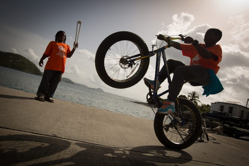 A young kid wheelies his bike in front of the Baton