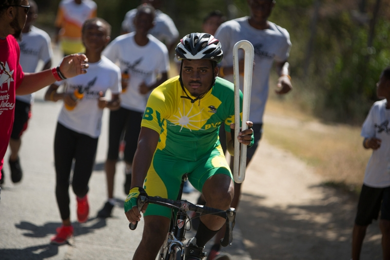 Cyclists Shaquil Samuels carries the Baton
