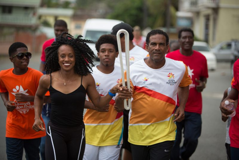 The Baton is carried by Deputy Premier Dr The Hon Kendrick Pickering and Olympic sprinter Tahesia Harrigan Scott